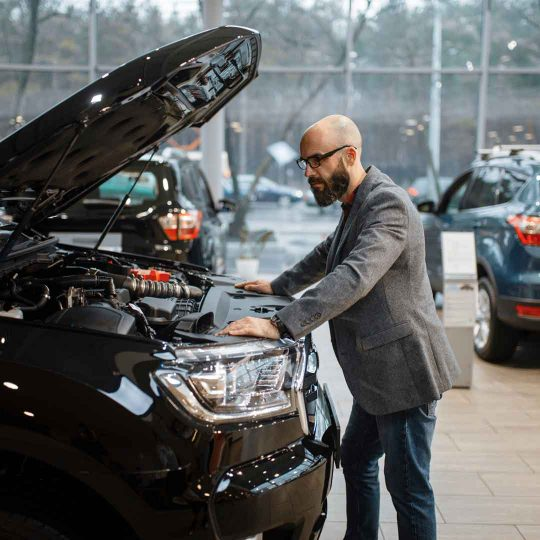 man at new truck with opened hood car dealership