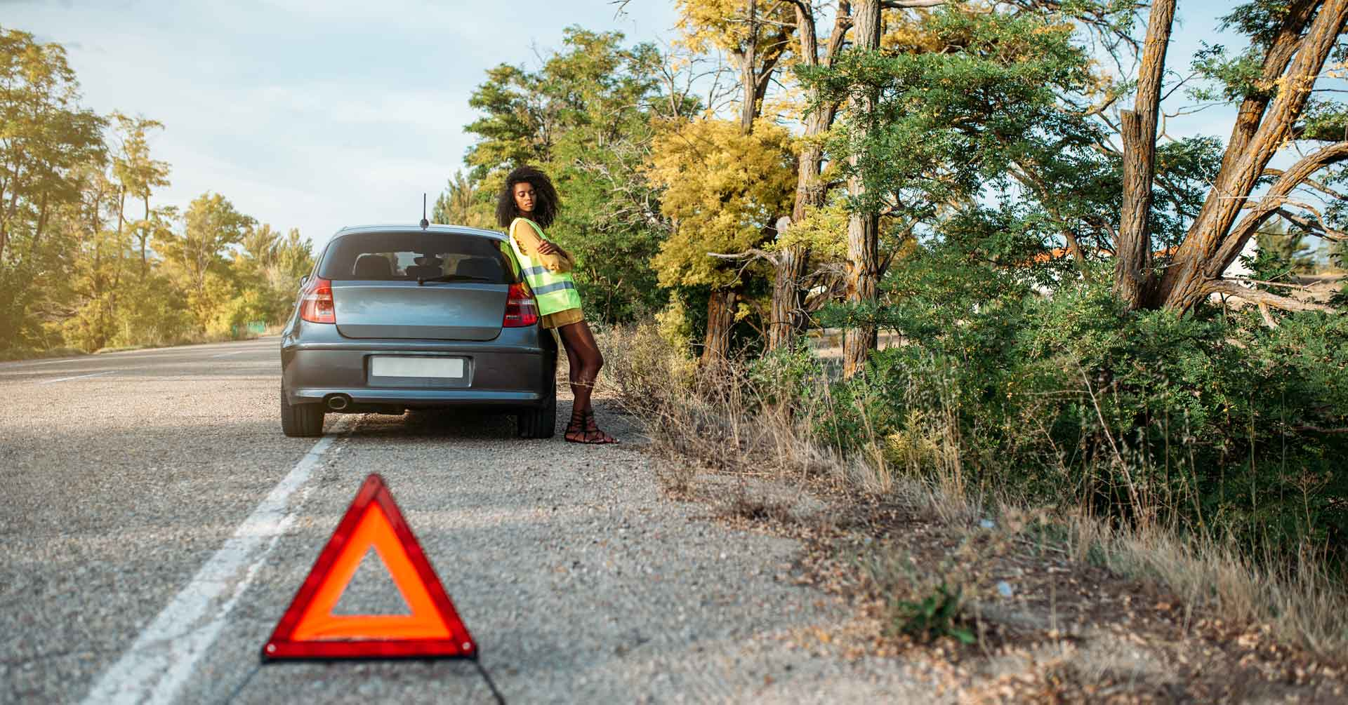 woman with broken car and triangle waiting for a jump start